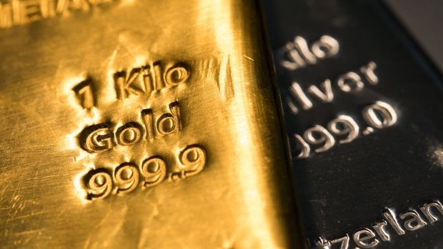 A one-kilogram gold bar sits on top of a one-kilogram silver bar at Gold Investments Ltd. bullion dealers in this arranged photograph in London, U.K., on Wednesday, July 29, 2020. Gold held its ground after a record-setting rally as investors awaited the outcome of a Federal Reserve meeting amid expectations policy makers will remain dovish, potentially spurring more gains. Photographer: Chris Ratcliffe/Bloomberg