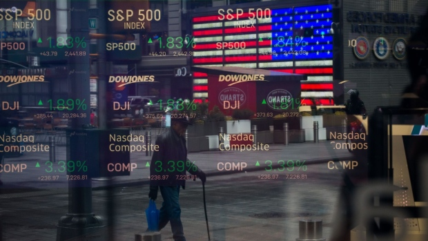 Monitors displaying stock market information are seen through the window of the Nasdaq MarketSite in the Times Square neighborhood of New York, U.S., on Thursday, March 19, 2020. New York state Governor Andrew Cuomo on Thursday ordered businesses to keep 75% of their workforce home as the number of coronavirus cases rises rapidly.