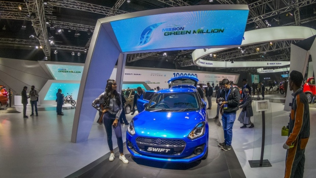 A member of the media takes a photograph of a Maruti Suzuki Ltd. Swift hatchback on display at the Auto Expo 2020 in Noida, Uttar Pradesh, India, on Wednesday, Feb. 5, 2020. The motor show opens to the public on Feb. 7 and runs through Feb. 12. Photographer: Prashanth Vishwanathan/Bloomberg