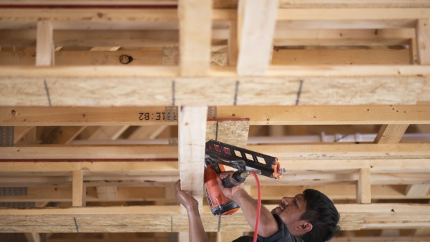 A worker uses a nail gun in a home under construction at a Romanelli and Hughes Building Co. subdivision in Dublin, Ohio, U.S., on Thursday, July 9, 2020. The U.S. housing market this week surprised economists by rallying in the midst of a pandemic. But the coronavirus may drag down home values after all. Photographer: Ty Wright/Bloomberg