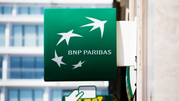 A BNP Paribas SA logo sits on a sign outside a BNP Paribas bank branch in Paris, France, on Tuesday, July 18, 2017. BNP Paribas agreed to pay $246 million to settle Federal Reserve allegations that the bank failed to keep its currency traders from using electronic chatrooms to manipulate prices. Photographer: Christophe Morin/Bloomberg