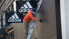 A worker removes screws from wood boarded up on the windows of an Adidas AG store in San Francisco, California, U.S., on Tuesday, June 16, 2020. San Francisco moved into Phase 2B of reopening on Monday, opening up outdoor dining and allowing customers to go inside retail stores to shop.