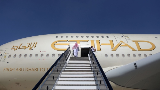 An attendee enters an Airbus SE A380 passenger aircraft, operated by Etihad Airways PJSC, during the 15th Dubai Air Show at Dubai World Central (DWC) in Dubai, United Arab Emirates, on Monday, Nov. 13, 2017. The biennial Dubai expo is an important venue for manufacturers to secure deals for their biggest and most expensive jetliners.
