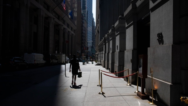 A pedestrian walks along Wall Street near the New York Stock Exchange (NYSE) in New York, U.S., on Monday, July 20, 2020. U.S. stocks fluctuated in light trading as investors are keeping an eye on Washington, where lawmakers will begin hammering out a rescue package to replace some of the expiring benefits earlier versions contained.