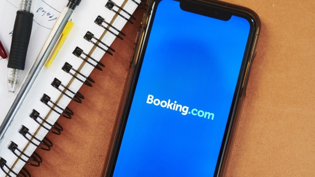 The logo for Booking Holdings Inc. is displayed on a smartphone in an arranged photograph taken in the Brooklyn borough of New York, U.S., on Sunday, May 10, 2020. In a matter of months, the coronavirus reset the clock on a decades-long aviation boom that's been one of the great cultural and economic phenomena of the postwar world. Photographer: Gabby Jones/Bloomberg