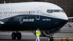 Crewman tow in a Boeing Co. Max 737 jet after landing at King County International Airport in Seattle, Washington, U.S., on Friday, Jan. 29, 2016. Boeing Co.'s newest 737 jetliner gunned its engines and headed into rain-streaked skies Friday, with profit and pride riding on its wings.