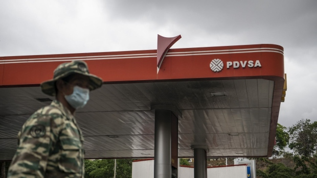 A soldier wearing a protective mask stands guard outside a Petroleos de Venezuela SA (PDVSA) gas station in Caracas, Venezuela, on Monday, June 1, 2020. Venezuela's President Nicolas Maduro said fuel prices would increase starting in June, a historic policy shift after decades of subsidies that have allowed Venezuelans to essentially fill their tanks for free. Photographer: Carlos Becerra/Bloomberg