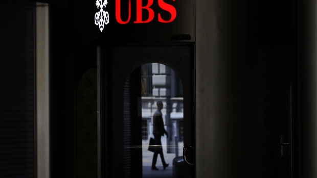 A pedestrian is reflected in a door of a UBS Group AG bank branch in Zurich, Switzerland, on Friday, April 17, 2020. A UBS appeal of a record 4.5 billion-euro ($4.9 billion) French fine for helping clients stash undeclared funds in offshore accounts was postponed over concerns related to coronavirus pandemic, according to people familiar with the case. Photographer: Angel Garcia/Bloomberg