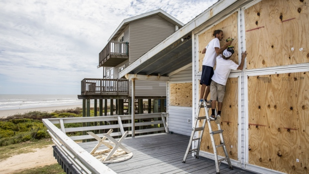 Workers board up a beach-front house ahead of Hurricane Laura in Galveston, Texas, U.S., on Tuesday,