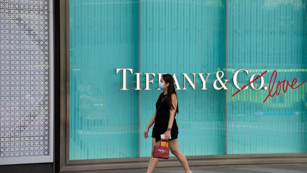 "A pedestrian wearing a protective mask walks past a Tiffany & Co. luxury goods store in Singapore, on Monday, Feb. 10, 2020. Singapore last week raised its disease response level to the same grade used during the SARS epidemic, as it braced for what Prime Minister Lee Hsien Loong said was a ""major test for our nation."" Photographer: SeongJoon Cho/Bloomberg"