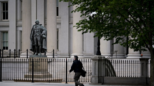 A pedestrian walks near the U.S. Treasury building in Washington, D.C., U.S., on Wednesday, May 20, 2020. Treasury Secretary Steven Mnuchin said he plans to use all of the $500 billion that Congress provided to help the economy through direct lending from his agency and by backstopping Federal Reserve lending programs.