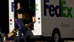 A FedEx Corp. worker wearing a protective mask unloads a truck in downtown Dallas, Texas, U.S., on Wednesday, May 27, 2020. Texas Governor Greg Abbott allowed bars—along with rodeos, bowling alleys and bingo halls—to open their doors at reduced capacity in the second phase of the state's plan to restart the economy after shutting down in early April to slow the coronavirus.