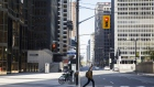 A pedestrian crosses Bay Street in the financial district of Toronto, Ontario, Canada, on Friday, May 22, 2020. Whether the PATH, a subterranean network that provides connections between major commuter stations, over 80 properties, including the headquarters of Canada's five largest banks, and 1,200 retail spots, can return to its glory days will depend initially on how quickly Bay St. firms return workers to their offices.
