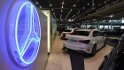 An illuminated Mercedes-Benz trident logo sits on display near luxury automobiles, manufactured by Daimler AG, in the automaker's showroom in Munich, Germany, on Tuesday, July 7, 2020.