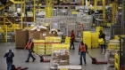 Employees pull pallet trucks at the Amazon.com Inc. fulfillment center in Robbinsville, New Jersey, U.S., on Monday, Nov. 27, 2017.