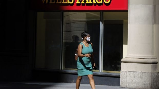 A pedestrian wearing a protective mask walks past a Wells Fargo & Co. bank branch in New York, U.S., on Thursday, July 9, 2020. Wells Fargo is scheduled to release earnings figures on July 14. Photographer: Peter Foley/Bloomberg