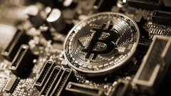 A coin representing Bitcoin cryptocurrency sits on a computer circuit board in this arranged photograph in London, U.K., on Tuesday, Feb. 6, 2018. Cryptocurrencies tracked by Coinmarketcap.com have lost more than $500 billion of market value since early January as governments clamped down, credit-card issuers halted purchases and investors grew increasingly concerned that last year's meteoric rise in digital assets was unjustified. Photographer: Chris Ratcliffe/Bloomberg