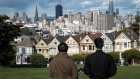 People stand in Alamo Square overlooking the city skyline in San Francisco, California, U.S., on Thursday, March 26, 2020.