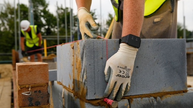 A bricklayer uses wearable technology, which vibrates when wearer breaches social distancing guidelines, on a Bewley Homes Plc residential construction site in Ash, near Farnborough, U.K. on Friday, June 12, 2020. New practices on construction sites will incorporate social distancing and workers in two-person tasks will use personal protective equipment. Photographer: Luke MacGregor/Bloomberg