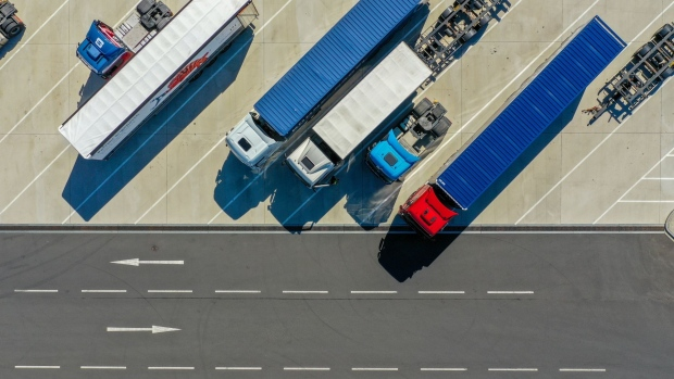 Trucks and trailers sit parked at the Kuehne + Nagel International AG logistics center in this aerial view in Haiger, Germany, on Thursday, Aug. 6, 2020. Transport group Kuehne + Nagel's first-half earnings beat estimates, aided by cost management as its revenue declined. Photographer: Alex Kraus/Bloomberg