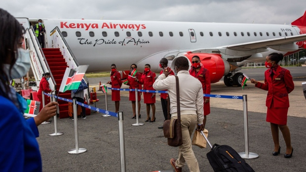 Crew members from Kenya Airways welcome a passenger onto an aircraft during a reopening ceremony at Jomo Kenyatta International Airport in Nairobi, on July 15. Photographer: Patrick Meinhardt/Bloomberg