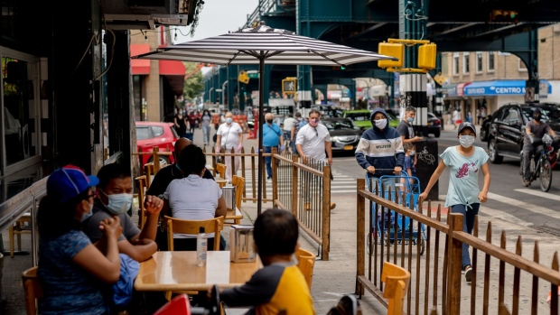 Pedestrians pass in front of customers sitting outside at a restaurant in in the Queens borough of New York.