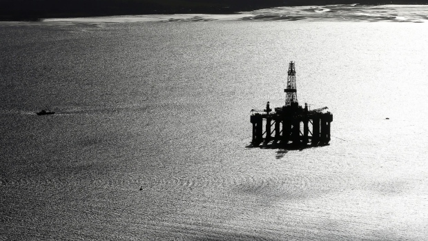 A boat passes a mobile offshore drilling unit in the Port of Cromarty Firth in Cromarty, U.K., on Wednesday, March 22, 2017.