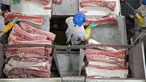 Butchers place pork ribs on a conveyor belt at a Smithfield Foods Inc. pork processing facility in Milan, Missouri, U.S., on Wednesday, April 12, 2017. Photographer: Daniel Acker/Bloomberg