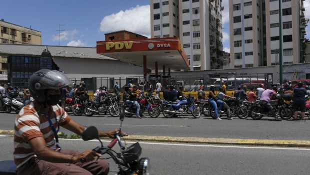Motorcyclists wearing protective masks wait in line for fuel in at a gas station in Caracas, on Aug. 14.
