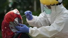 A healthcare worker dressed in personal protective equipment collects a swab sample from a resident at a mobile Covid-19 testing facility in Jakarta, Indonesia, on Wednesday, July 29, 2020. Total coronavirus infections in Indonesia surged past 100,000 amid an easing of physical-distancing rules to allow economic activity to resume, prompting President Joko Widodo to order health officials to focus on containing the disease in the nation's eight main provinces. Photographer: Dimas Ardian/Bloomberg