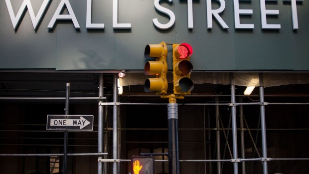 A traffic light stands in front of scaffolding surrounding 1 Wall Street near the New York Stock Exchange (NYSE) in New York, U.S., on Friday, Aug. 24, 2018.