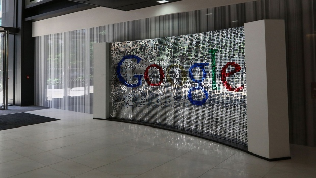 A visitor passes a sign featuring Google Inc.'s logo inside their U.K. headquarters at Six St Pancras Square in London. Photographer: Chris Ratcliffe/Bloomberg