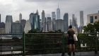 A man looks out at the Manhattan skyline in a Brooklyn neighborhood on September 29.
