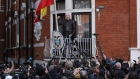 Julian Assange, founder of WikiLeaks, holds up a fist before speaking to media and supporters from a balcony at the Ecuadorian embassy in London, U.K., on on Friday, May 19, 2017. Assange hailed a Swedish decision to drop a rape probe against him, but said he won't leave the Ecuadorian embassy in London where he has sought refuge for the past five years as long as he remains a target in the U.S. and U.K.