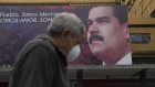 A pedestrian passes by a billboard featuring an image of Nicolas Maduro in Caracas. Photographer: Carlos Becerra/Bloomberg