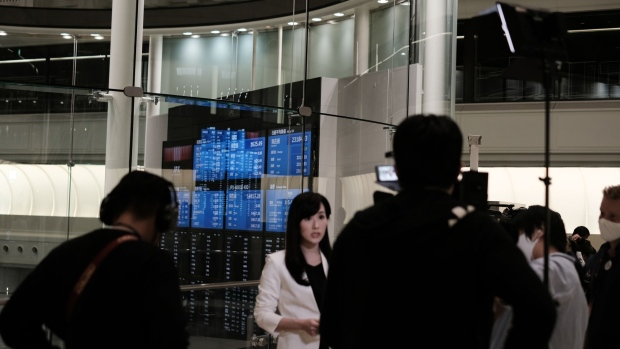 Members of the media work near a screen displaying share prices inside the Tokyo Stock Exchange (TSE), operated by Japan Exchange Group Inc. (JPX), in Tokyo, Japan, on Thursday, Oct. 1, 2020. The Tokyo Stock Exchange halted trading for the entire day Thursday on a hardware breakdown, freezing buying and selling in thousands of companies in the worst-ever outage for the world's third-largest bourse.