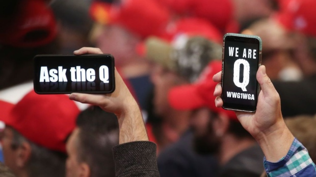 LAS VEGAS, NEVADA - FEBRUARY 21: Supporters of President Donald Trump hold up their phones with messages referring to the QAnon conspiracy theory at a campaign rally at Las Vegas Convention Center on February 21, 2020 in Las Vegas, Nevada. The upcoming Nevada Democratic presidential caucus will be held February 22. (Photo by Mario Tama/Getty Images) Photographer: Mario Tama/Getty Images North America