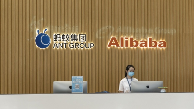 The Ant Group Co. logo and the Alibaba Group Holding Ltd. logo are displayed behind a reception desk at the company's headquarters in Hangzhou, China, on Monday, Sept. 28, 2020. Jack Ma's Ant Group is seeking to raise $17.5 billion in its Hong Kong share sale and won't seek to lock in cornerstone investors, confident there will be plenty of demand for one of the largest equity deals in the financial hub, according to people familiar with the matter. Photographer: Qilai Shen/Bloomberg