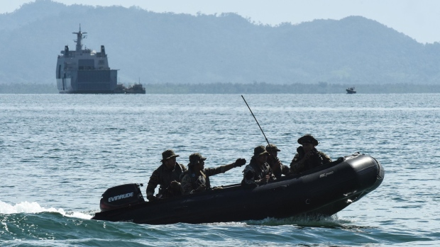 "AURORA PROVINCE, PHILIPPINES - MAY 15: A team of special warfare troops of the Philippine Navy patrol the coastline with the Philippine Navy ship, BRP Tarlac in the foreground on May 15, 2017 in Casiguran Province, Philippines. Philippines and U.S. troops held the annual ""Balikatan"" (shoulder-to-shoulder) joint military exercises with an approximately 6,000 participating troops, consisting of some 2,800 Philippine troops and 2,600 U.S. troops. The annual joint exercises are reportedly smaller in scale compared to previous years as directed by President Rodrigo Duterte, who has taken a softer stance than his predecessor toward territorial disputes with China in the South China Sea while expanding security ties with China and Russia. (Photo by Dondi Tawatao/Getty Images)"