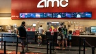 Customers wearing protective masks visit the concession stand at an AMC Entertainment Holdings Inc. movie theater in Austin, Texas, U.S., on Thursday, Aug. 20, 2020. AMC will be reopening more than 100 theaters across the country Thursday, about one-sixth of its locations, with plans to open more in the coming weeks.
