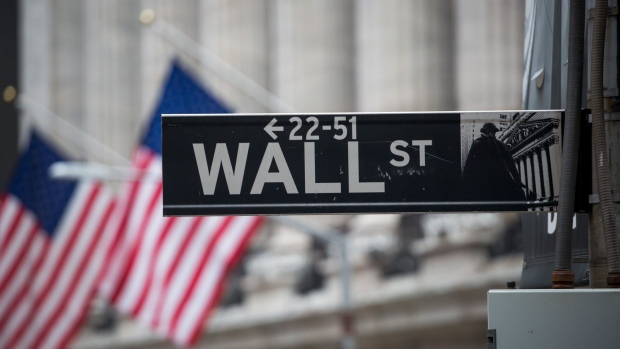 A Wall Street sign d in front of New York Stock Exchange. Photographer: Michael Nagle/Bloomberg