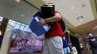 A shopper carries boxes of shoes at the Queens Center shopping mall in the Queens borough of New York on Sept. 9.