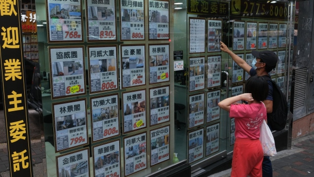 People look at advertisements displayed at a property agency in Hong Kong, China, on Sunday, May 31, 2020. Home prices in the world's priciest city for real estate have so far held up well amid the economic distress, declining barely more than 1% since January. Photographer: Roy Liu/Bloomberg