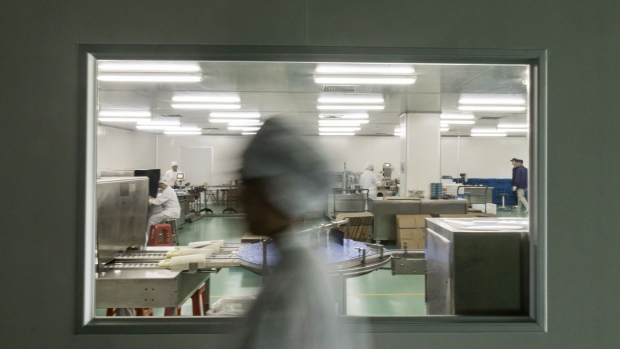 An employee walks past a production line at Guangzhou Pharmaceutical Holdings Ltd.'s Baiyunshan plant in Guangzhou, China, on Monday, Oct. 30, 2017. Midea Group Co., the world's biggest appliance maker, is working with Guangzhou Pharmaceutical to bring fully-automated dispensaries that can pick, package and distribute pills at hospitals and drugstores.