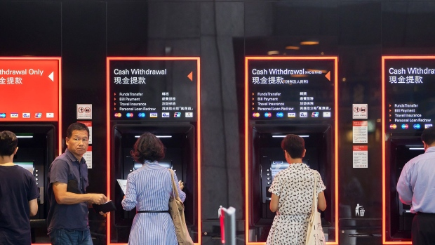 Customers use automated teller machines (ATM) at an HSBC Holdings Plc bank branch in Hong Kong, China, on Thursday, July 25, 2019. HSBC is scheduled to release interim earnings results on Aug. 5. Photographer: Paul Yeung/Bloomberg