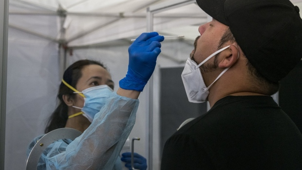 A medical worker wearing personal protective equipment (PPE) administers a rapid Covid-19 test to a traveler at San Francisco International Airport (SFO) in San Francisco, California, U.S., on Thursday, Oct. 15, 2020. United and Hawaiian Airlines are offering options for Covid-19 testing to passengers traveling to the state of Hawaii that will include at-home tests, drive-through testing, and in-person tests at the airport.