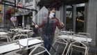 A worker wearing a protective mask carries a plexiglass shield while dismantling a restaurant's terrace in Montreal, Quebec, Canada, on Thursday, Oct. 1, 2020.