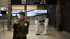 A French soldier stands guard near health workers at the Covid-19 test center in the arrival hall at Charles de Gaulle airport, operated by Airport de Paris, in Roissy, France, on Tuesday, Oct. 6, 2020. The European Union's battered aviation industry may soon get some relief from the confusingly wide range of travel curbs across the continent, as the bloc's governments seek agreement on a common threshold for imposing restrictions.