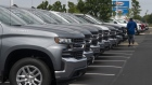 A customer looks over General Motors Co. Chevrolet Silverado trucks at a dealership in Grove City, Ohio.