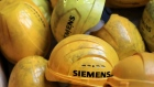 Branded yellow hard hats sit piled inside a Siemens factory in Berlin.